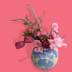 Pink flowers in a cream and blue splattered vase