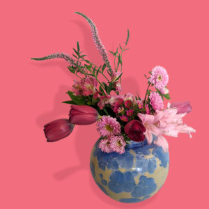Gorgeous cream and blue vase with pastel pink flowers artfully arranged