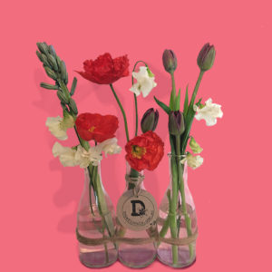 three glass bottles filled with hyacinth, tulips, sweet pea, and poppies