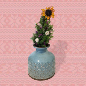 Small living christmas tree in a blue ceramic jug-like vase decorated with purple and white dried flowers and topped with a dried sunflower