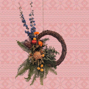 a dark wooden wreath with vibrant, colourful dried flower decoration