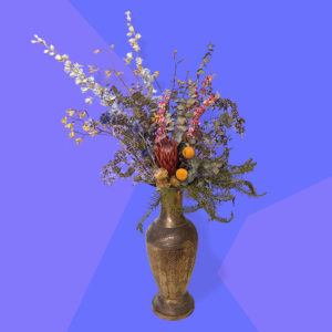 colourful and exuberant dried flower arrangement in decorative gold metal vase